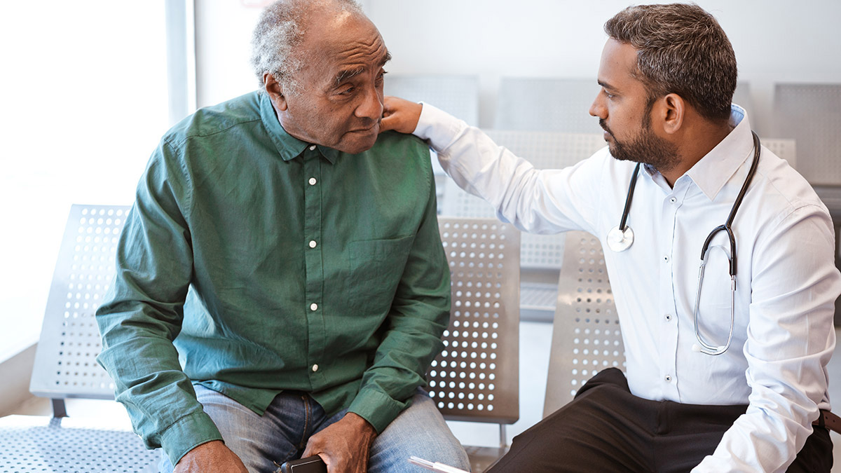 A medical professional sitting down with his hand on a man's shoulder who is also seated.